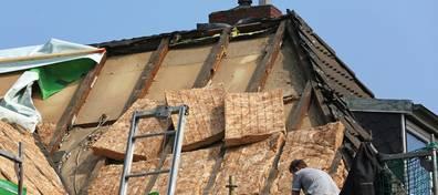 Dachsanierung, Dachdämmung, Altbau, Männer arbeiten auf einem abgedeckten Dach. Foto: Kara / fotolia.de