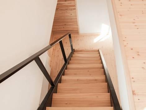 Treppenbau, DIN 18065, Blick eine schmale Holztreppe hinab, mit Geländer aus Glas und schwarzem Metall, Foto: stock.adobe.com / dzejdi