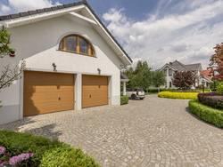 Bodenbelag Einfahrt, gepflasterte Einfahrt, Doppelgarage, im Hintergrund und hinter Hecken und Bäumen versteckt das Wohnhaus, Foto: stock.adobe.com / Photographee.eu