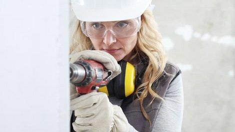 richtig bohren, Frau mit Helm und Schutzbrille bohrt in eine Wand, Foto: visivasnc / stock.adobe.com