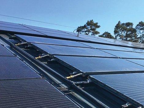 Röhrenkollektoren oder Flachkollektoren, Blick von schräg oben auf eine Dachfläche mit Hybridkollektoren, Foto: Solink